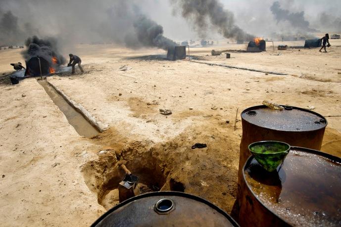 Recuperation de petrole a la raffinerie d'Al Mansoura, controlee par les djihadistes de l'Etat Islamique